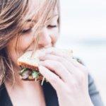 サンドイッチにかぶりつく女性